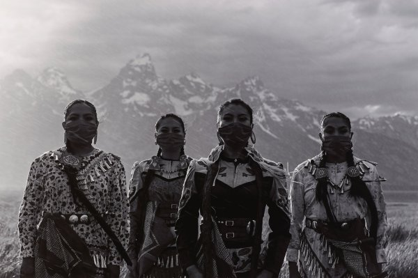 Black and white photograph with four Native American women wearing jingle dresses, with bandanas covering faces; Grand Tetons in background.