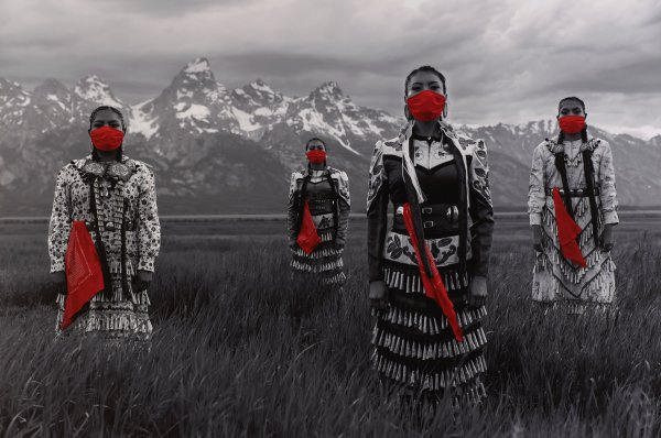 Black and white photograph of four Native American women wearing jingle dresses, standing in field with Grand Tetons in background. Bandanas covering womens faces and bandanas tucked in belts printed in red.