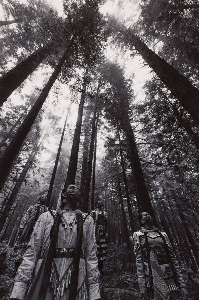 Black and white photograph with four Navajo women wearing jingle dresses, with bandanas covering their faces, standing at the base of tall redwood trees.