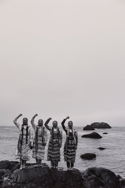 Black and white photograph with four Native American women, each with one fist raised, standing on boulders at water's edge.