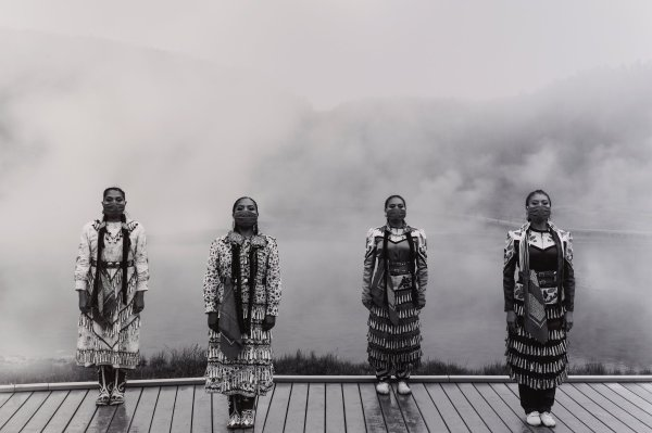 Black and white photograph with four Native American women wearing jingle dresses and face-covering bandanas, standing apart on wooden boardwalk, clouds in background