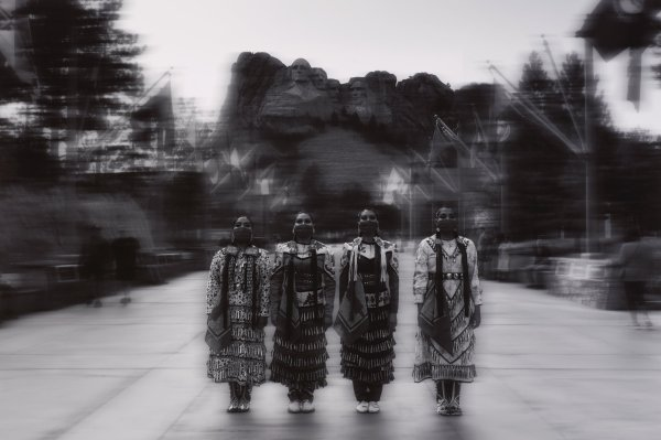 Black and white photograph of four Native American women wearing jingle dresses and face-covering bandanas, blurred Mount Rushmore in background.