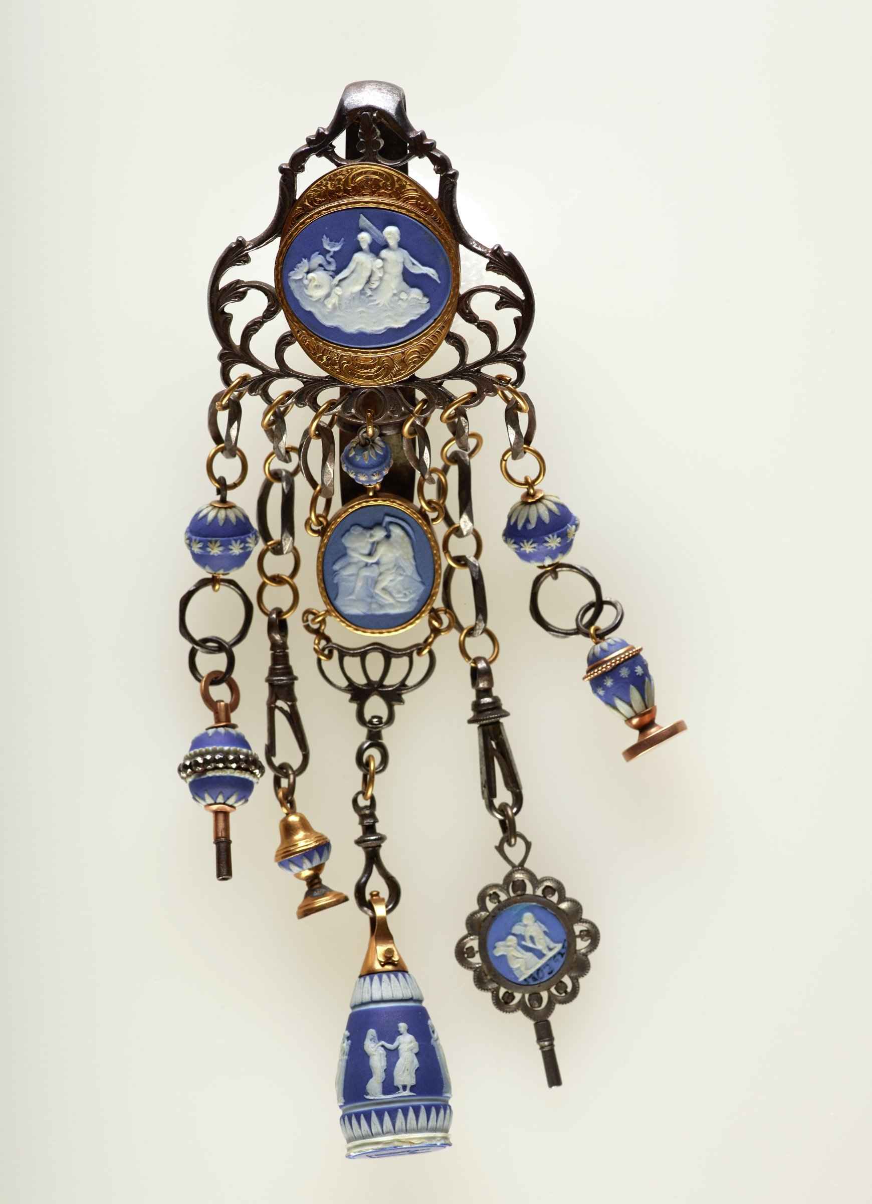 Chatelaine comprised of three blue and white jasper medallions and six beads mounted as pendants, watch keys, and seals, and a solid blue jasper seal with polished surface mounted in steel and gold with a hook on the back, the entire piece with five hanging elements suspended from a central element comprised of a jasper medallion with a scene of two figures riding a sea serpent set in an engraved gold mount, the first hanging element with two beads on a steel and gold chain, the lower bead with a band of cut steel diamonds functions as a watch key; the second element is a steel and gold chain with a hook from which hangs a jasper and gold seal (the plate is not engraved); the third element, the longest central element, includes a jasper bead on a steel chain above a jasper medallion of a seated figure with scythe, below this the sold blue jasper seal decorated with classical figures around, the plate likewise with two classical figures; the fourth hanging element comprised of a steel and gold chain from which hangs a two-sided blue and white jasper medallion set in a steel mount that functions as a watch key, the medallion with scenes of Psyche bound by Cupid, and two Cupids; the fifth and last hanging element consists of a similar chain with a jasper bead and a gold mounted jasper seal.