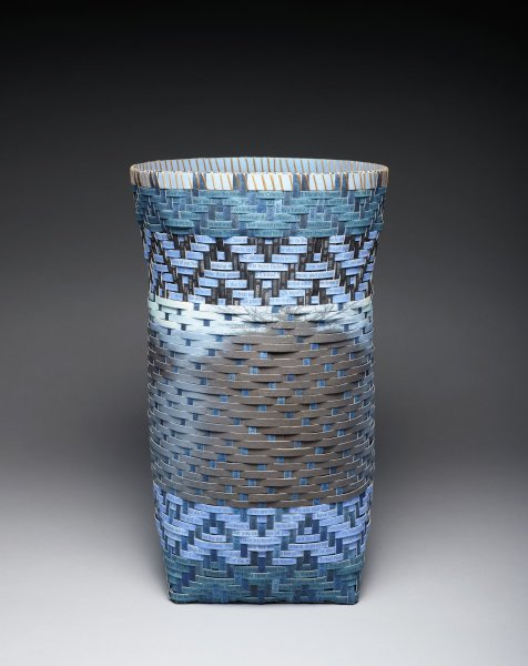 Vertical woven paper basket with round mouth and square bottom, in Cherokee water pattern; paper dyed shades of blue, lavender, and black. Photograph of Tuckasegee River in central band; text written on paper weaving strips drawn from David Archimbault's speech to United Nations in response to Dakota Access Pipeline on Standing Rock Sioux Reservation.