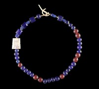 To the loop is attached a string of beads on a buckskin thong. There are twenty three spherical blue, eight spherical red, four large blue angular, six small blue angular; one piece of pearl from a knife handle