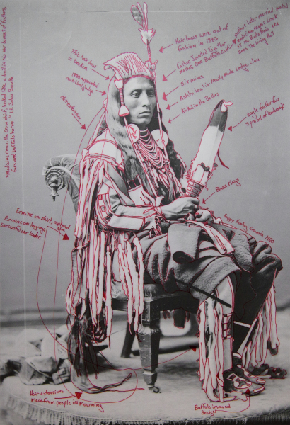 Artist-manipulated digitally reproduced photograph by C.M. (Charles Milton) Bell; subject is Peelatchiwaaxpáash / Medicine Crow (Raven) seated, full figure, three-quarter view; elements of regalia outlined in red, and text annotations in red radiate from figure.