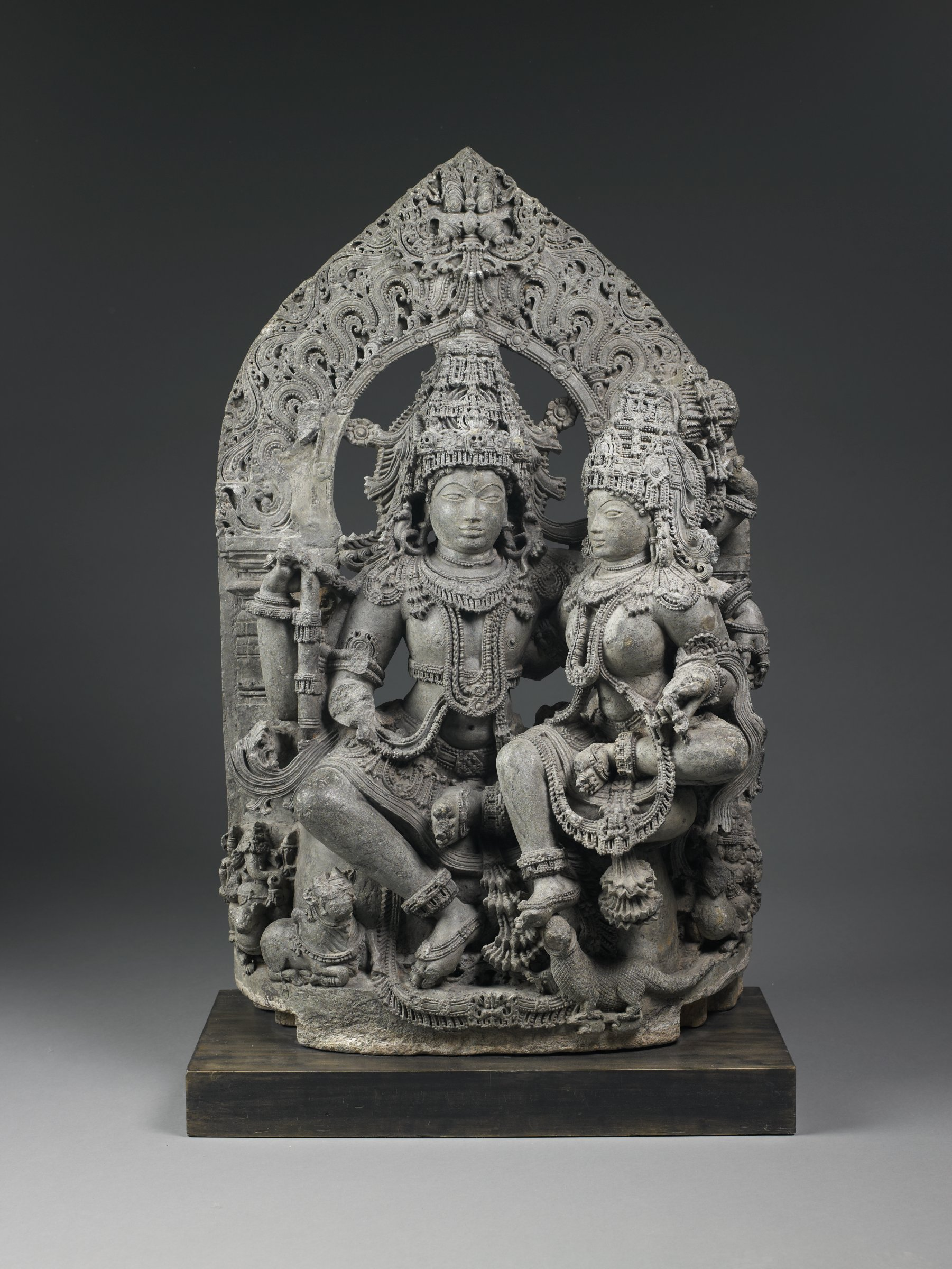 Large, highly detailed sculpture of four-armed Siva with skull-adorned diadem, holding a double-sided (damaru) drum in upper proper left hand, lower proper left arm embracing the Goddess seated upon his lap. His zebu bull is by his pendent proper right leg.  Parvati (as Gauri) with a iguana vahana as well as Ganesha riding his rat (lower left) and Kartikeya riding his peacock (lower right). Face-of-glory (kirtimukha) at mandorla's peack with waved cloud/foliate motifs.