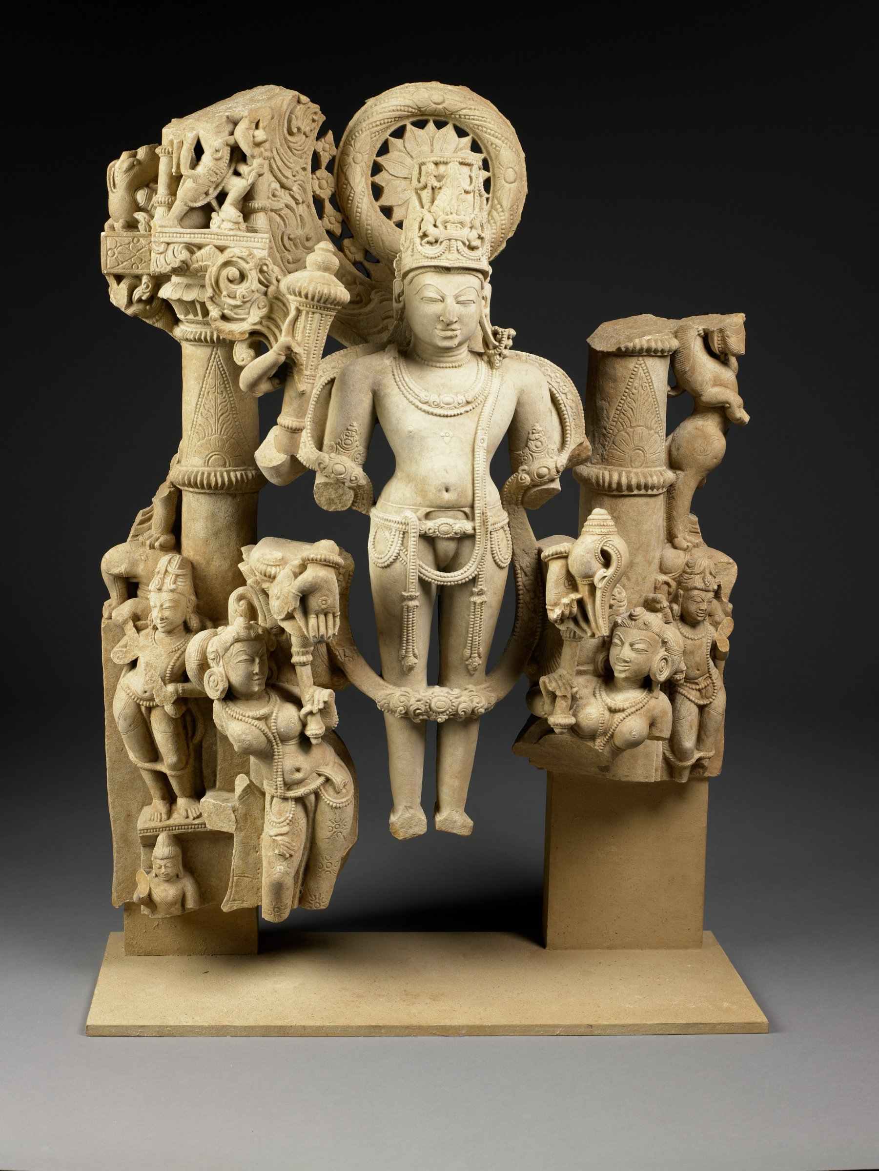 High relief sculpture depicting a four-armed iconic form of Vishnu retaining mace and conch and boon-granting gesture; figure wears highly decorative conical crown, jewelry and floral garland, lotus halo framing head. Two female attendents at legs,