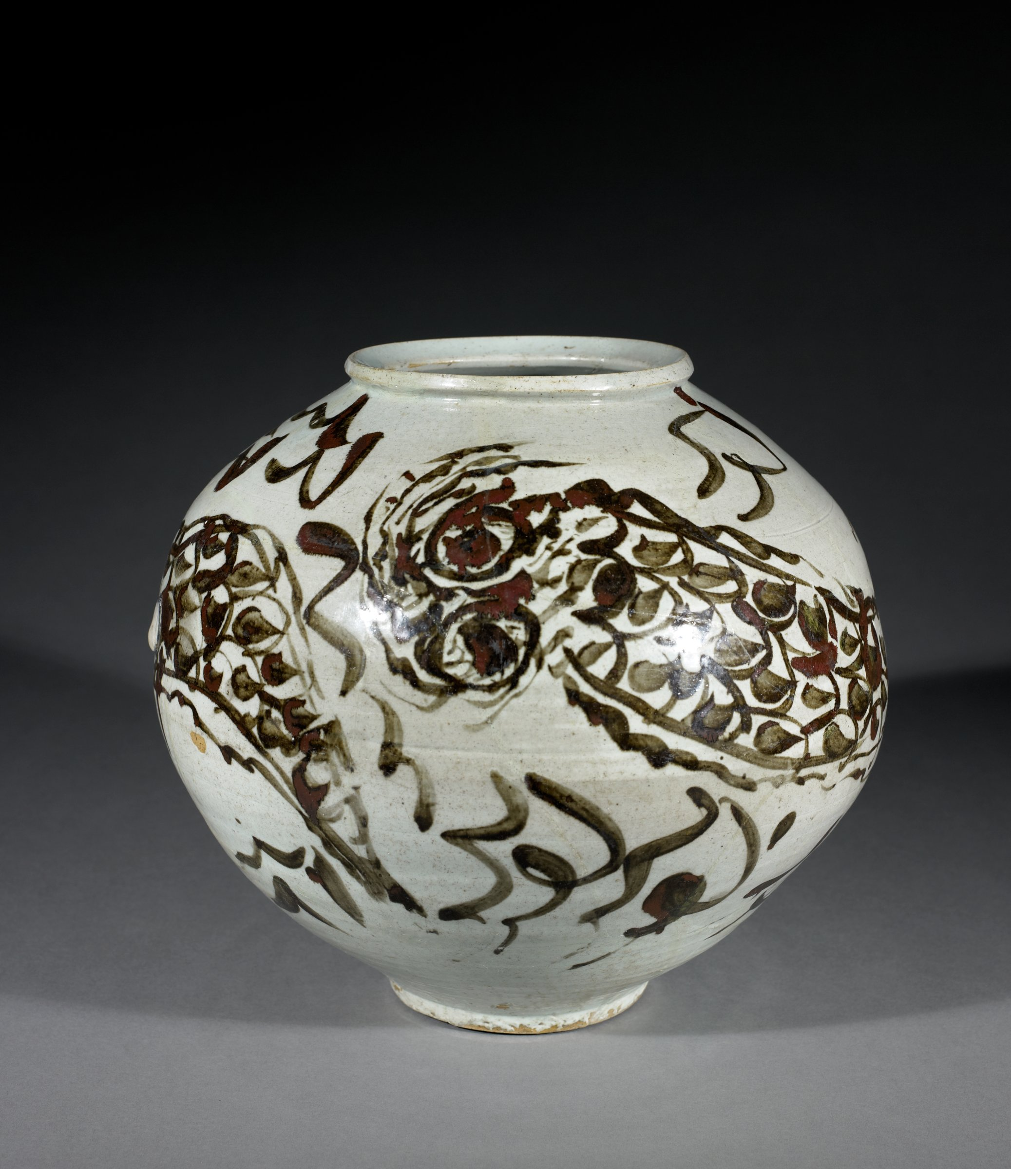 This jar was made in two halves, as evidenced from the groove in the center where the two pieces were joined. The jar was then decorated with a freely drawn dragon then fired. The numerous imperfections in the clay body are typical of 17th century pieces and in the Korean mind give character to each jar. Likewise, the brown painting displays subtle gradations and variations in texture that enliven the picture of the dragon.