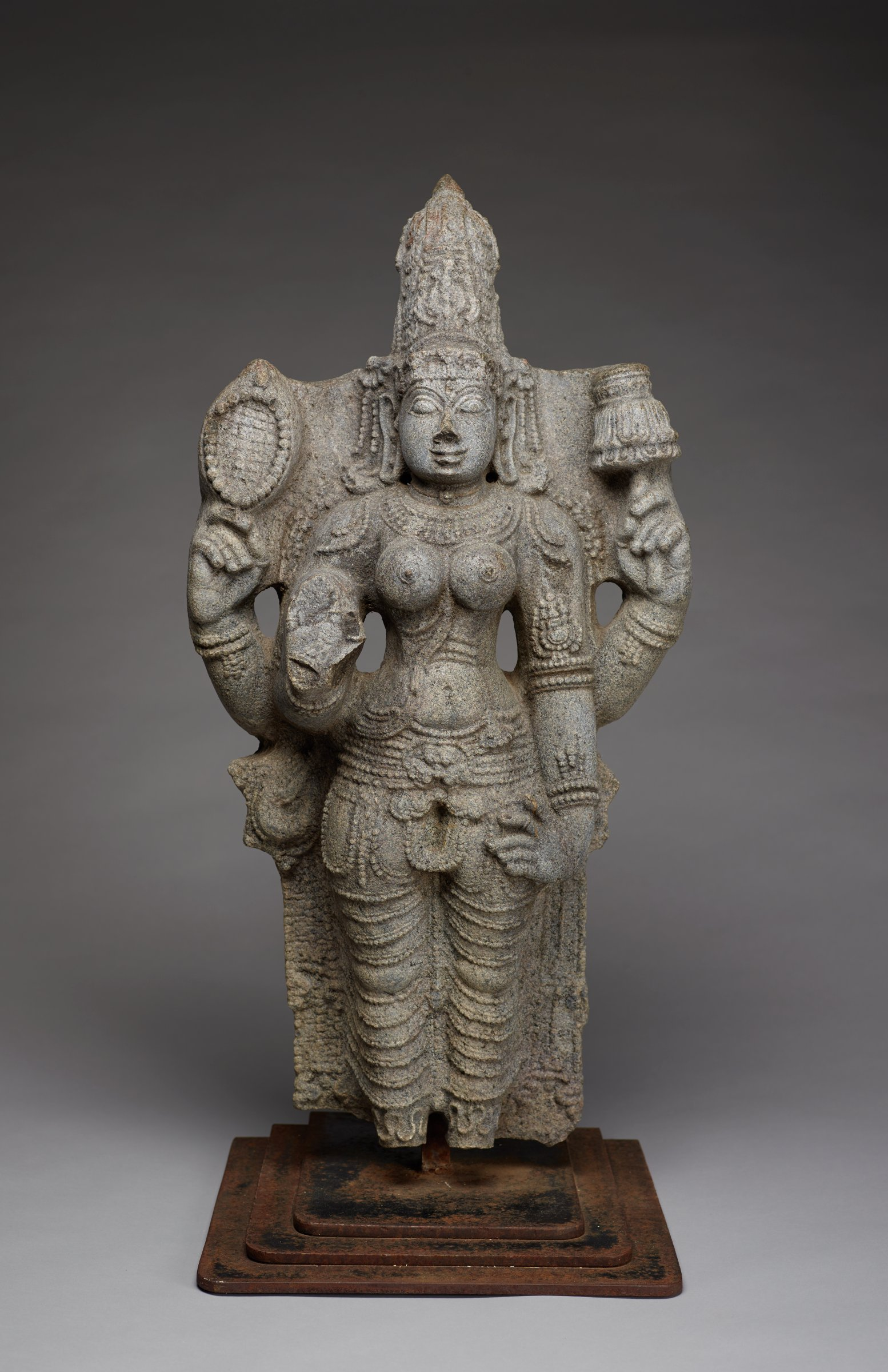 A standing figure of Lakshmi with four arms. Attributes she is holding include a rosary and a lotus in her uppermost arms. Elaborate crown and jewelry. Lower right hand is missing.