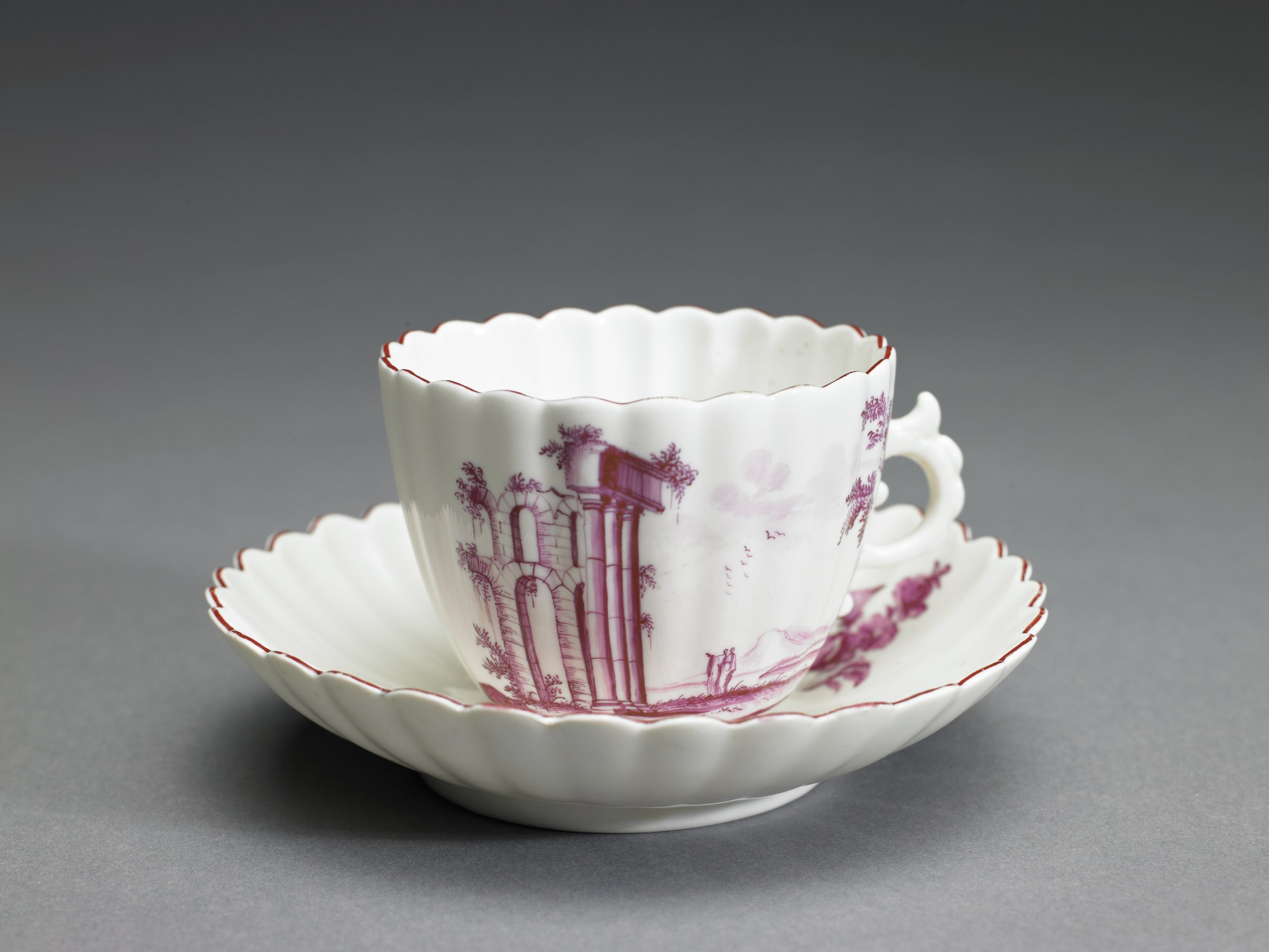 A soft-paste, white porcelain cup and saucer with overglaze puce enamel color, the cup fluted and with scalloped edge, painted with a design of ruins in a landscape, with scroll handle, the conforming saucer likewise fluted and with scalloped edge and painted with a similar design.