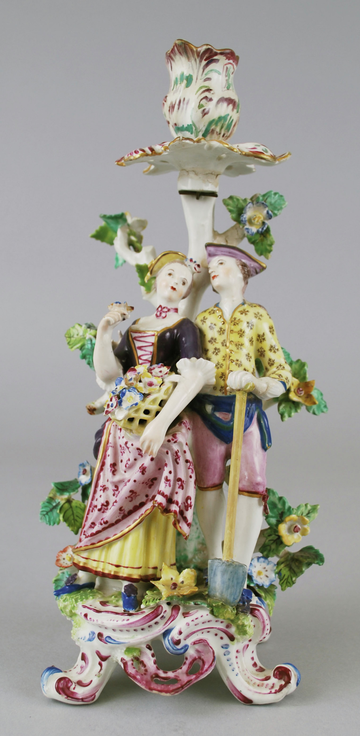 Soft-paste porcelain candlestick comprised of a figural group featuring a male gardener with spade and his female companion holding a basket of flowers, both wearing hats, their clothing decorated in bright enamel colors, standing on a scrolled base highlighted in blue and puce, behind them a flowering tree that extends upward to become a single candleholder and bobeche in the form of petals and highlighted in green and puce.