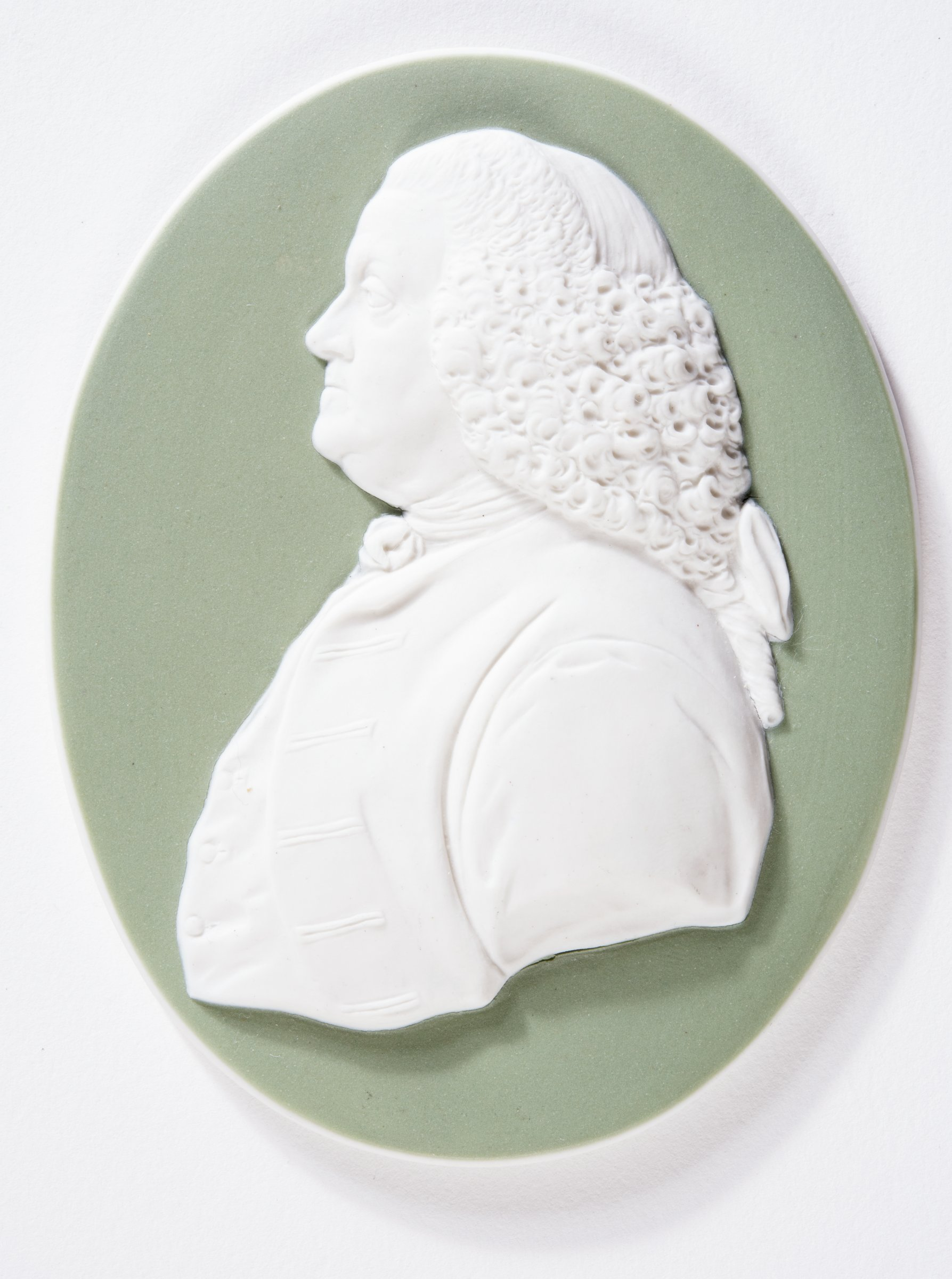 Oval portrait medallion of white jasper with green jasper dip and white relief decoration with the bust of Benjamin Franklin in profile left.