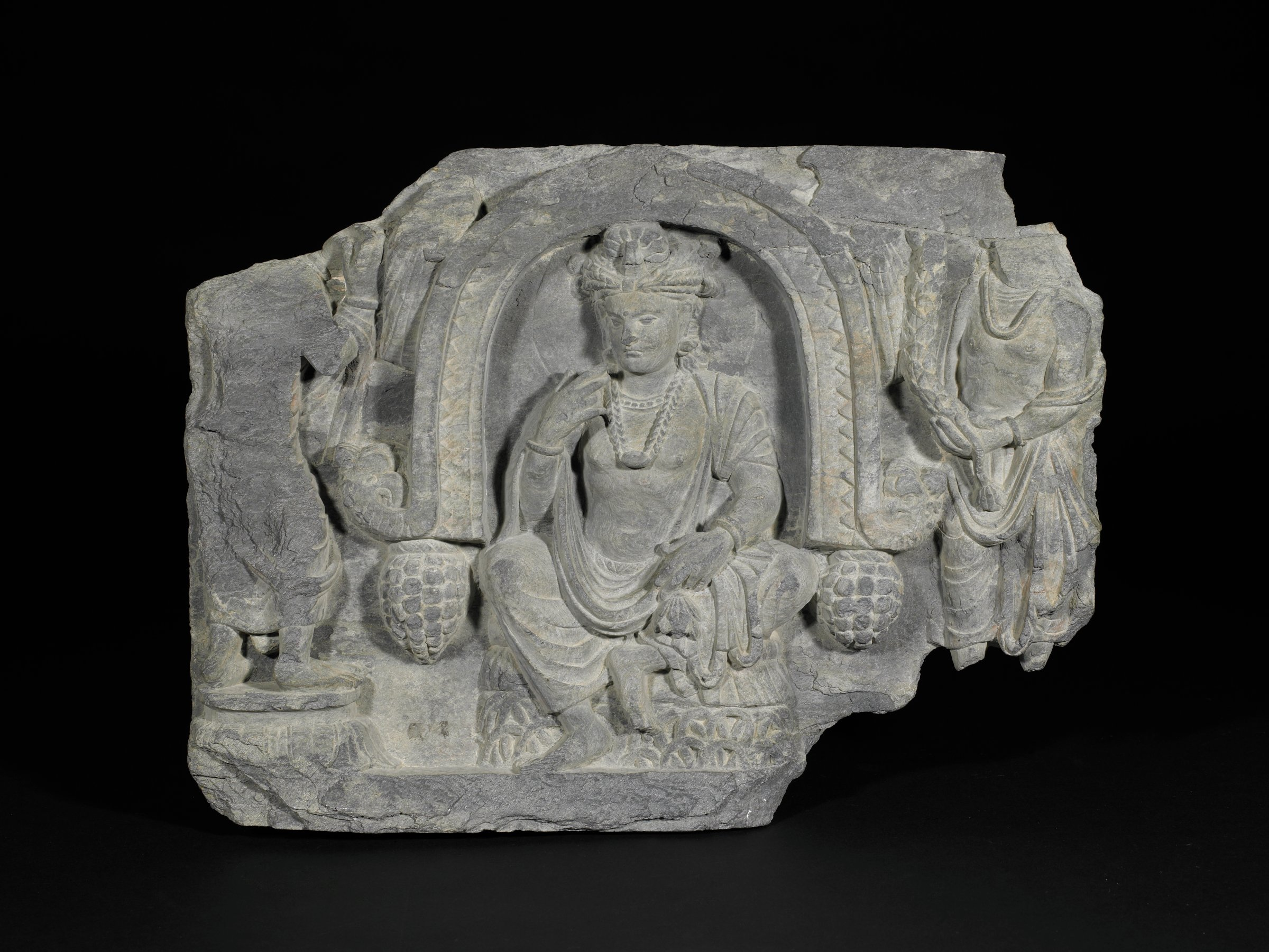 Pensive Bodhisattva Seated in Arch Decorated with Custard Apples and Bird Heads with two floral-garland bearing attendants