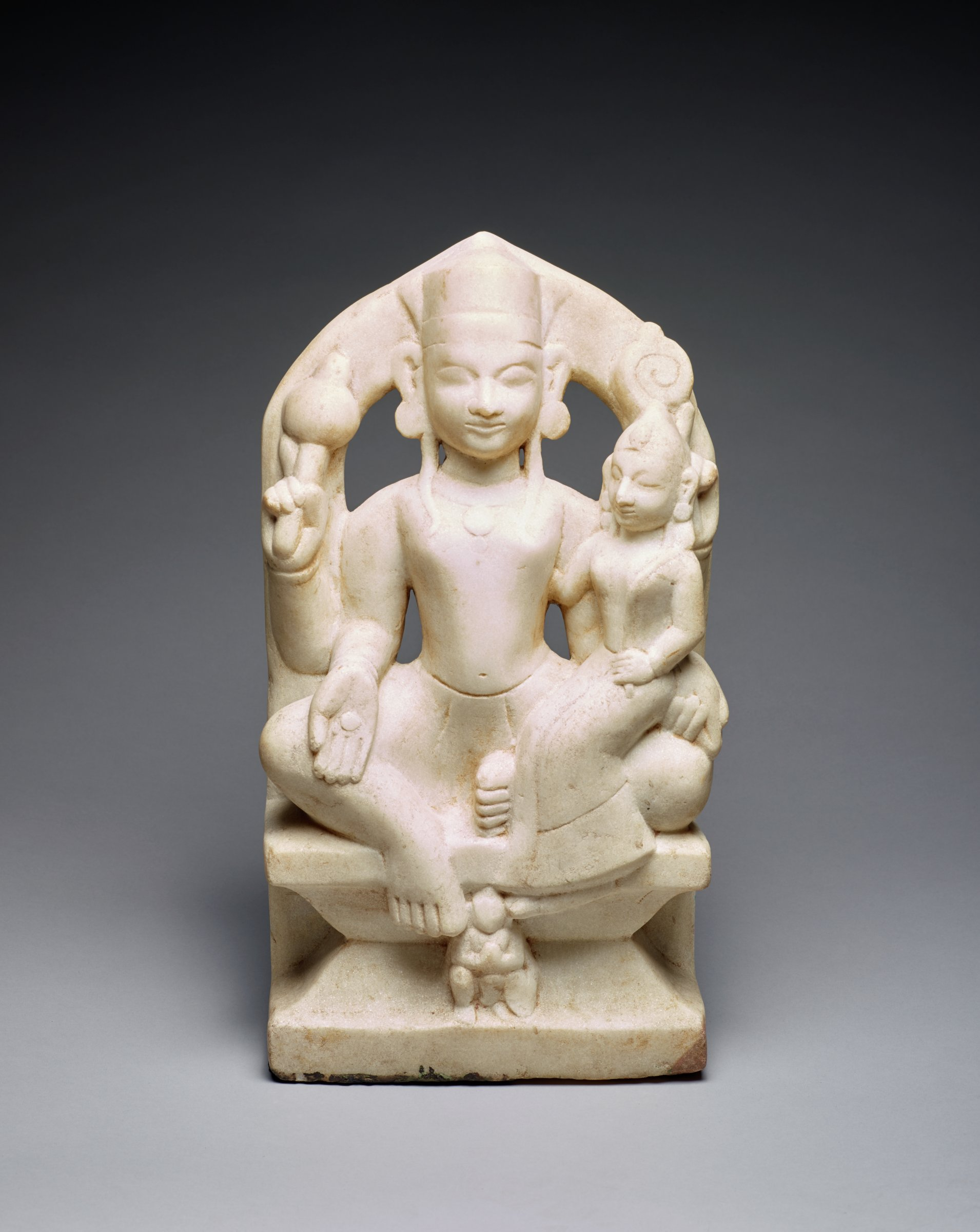 Upper two hands hold a mace and a discus, lowered proper left hand holds a conch while lowered proper right hand makes a boon-granting gesture. Seated in royal-east posture with Lakshmi on proper left leg. Kneeling garuda below.