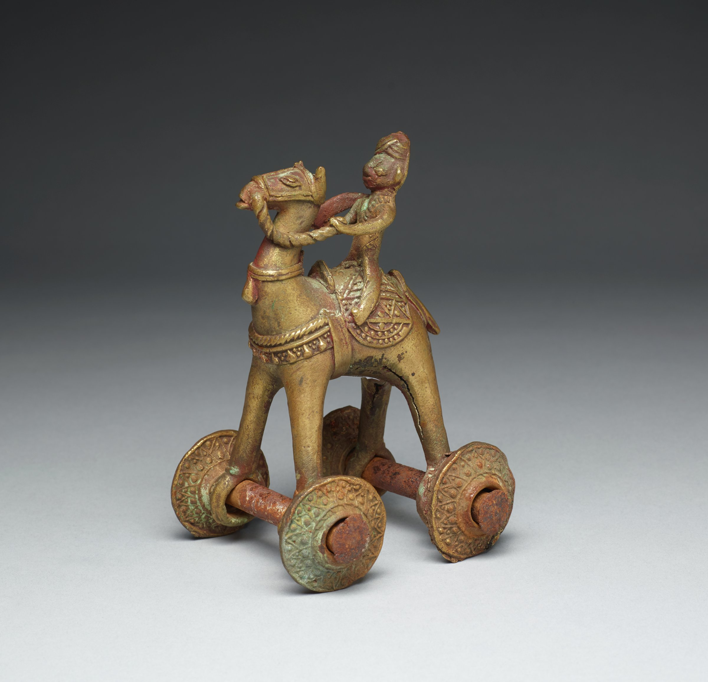 Turban-wearing equestrian rider mounted on caparisoned horse on wheels