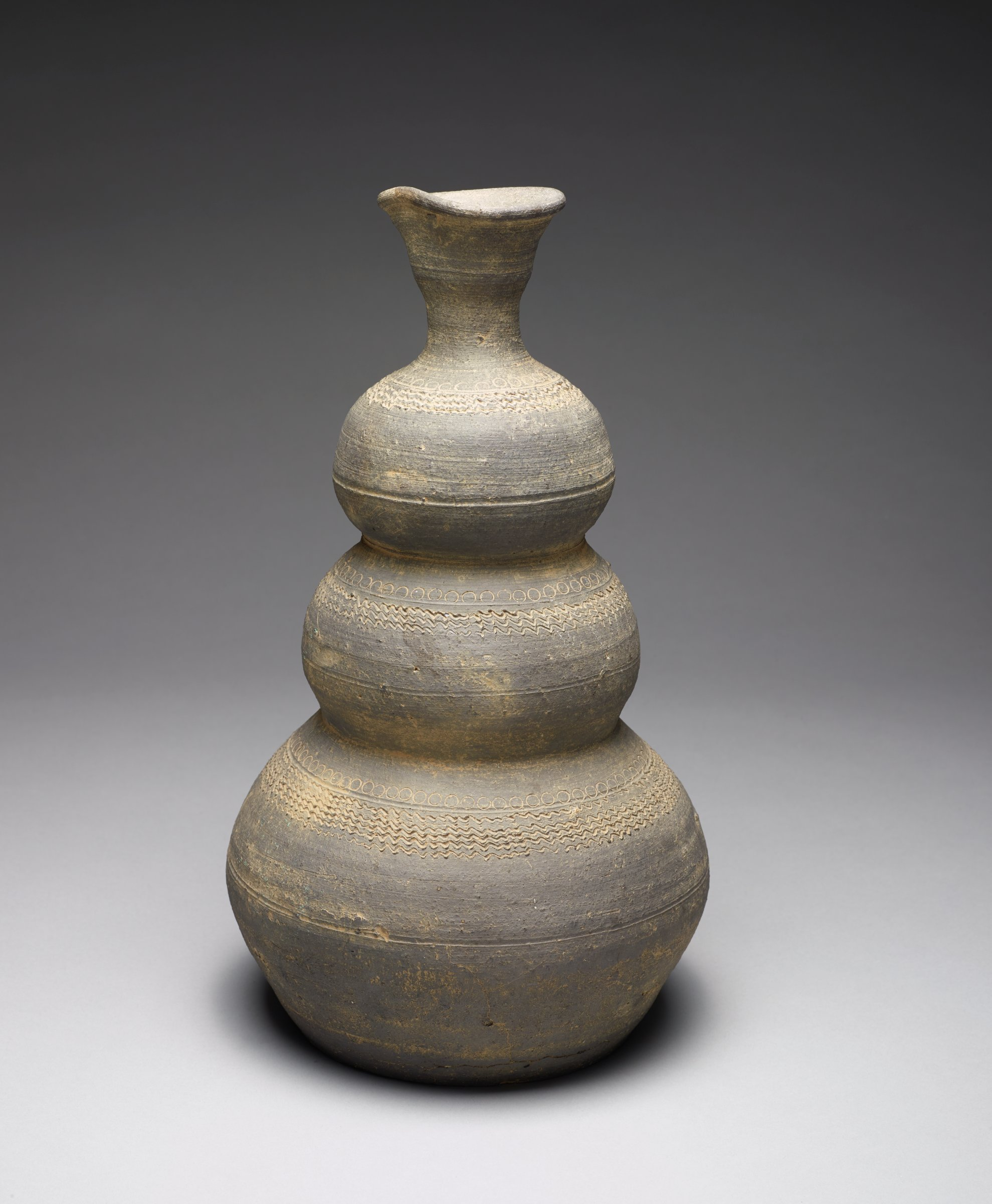 Triple-Gourd Shapled Bottle with Flared Mouth, Stamped Circles and Carved Wave MotifsThickly potted; closely related to 1983.126