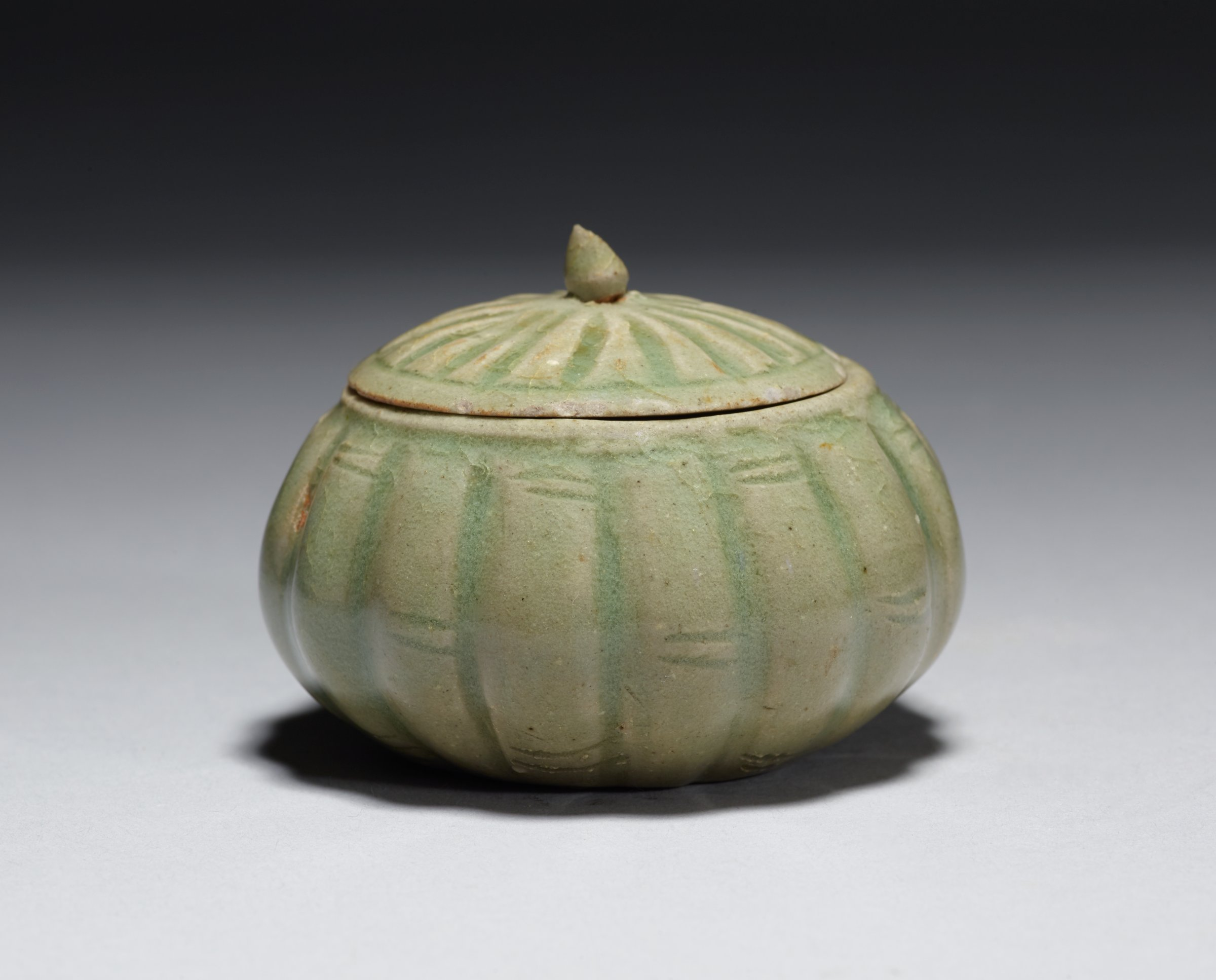 Jar is vertically incised to simulate bamboo or basket work; cover is marked by radiating grooves. Lid is chipped on lip and finial.