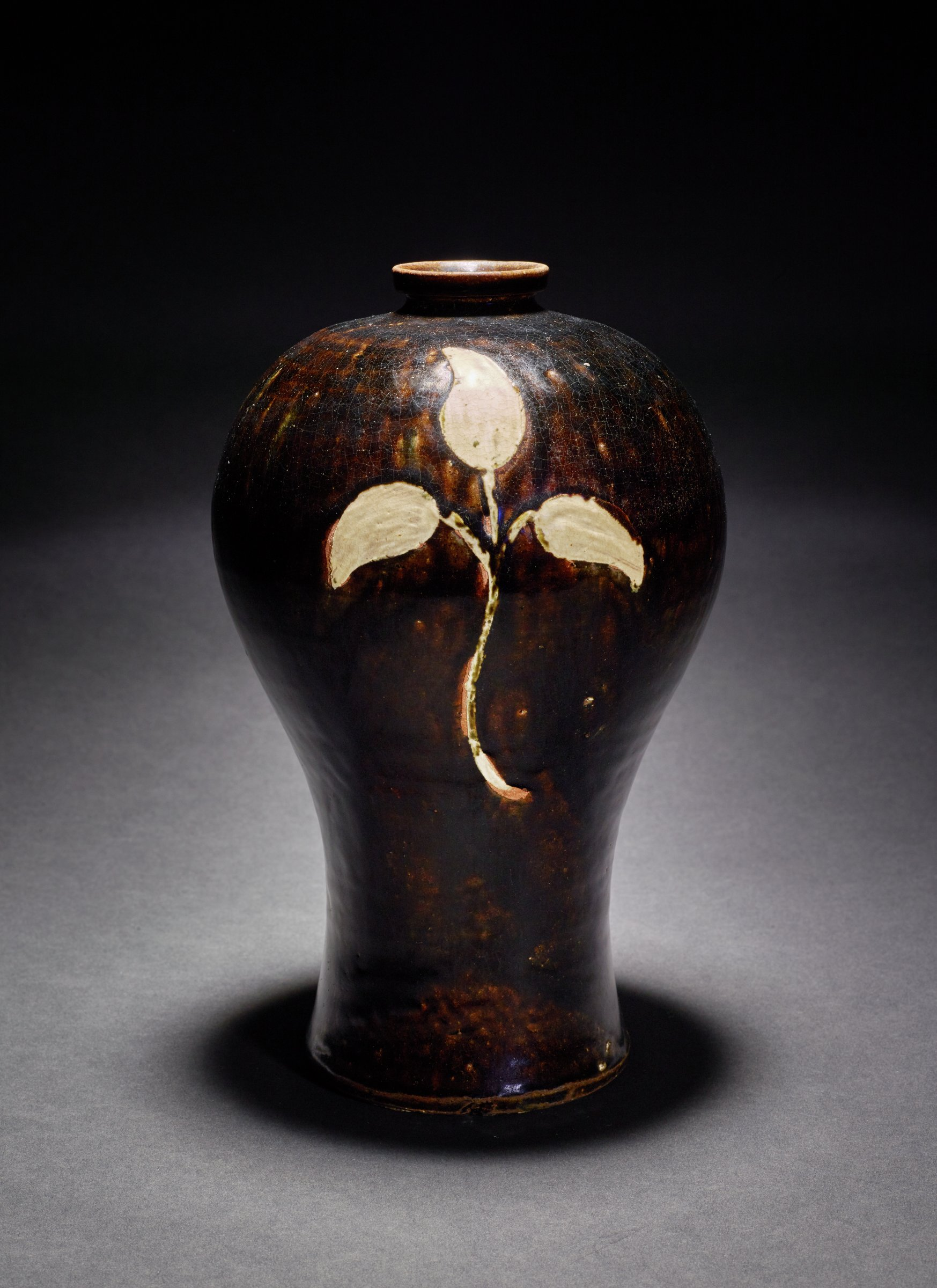 Celadon glazed tall vase with underglaze iron-brown and inlaid design of ginseng leaves. Chipped under-lip