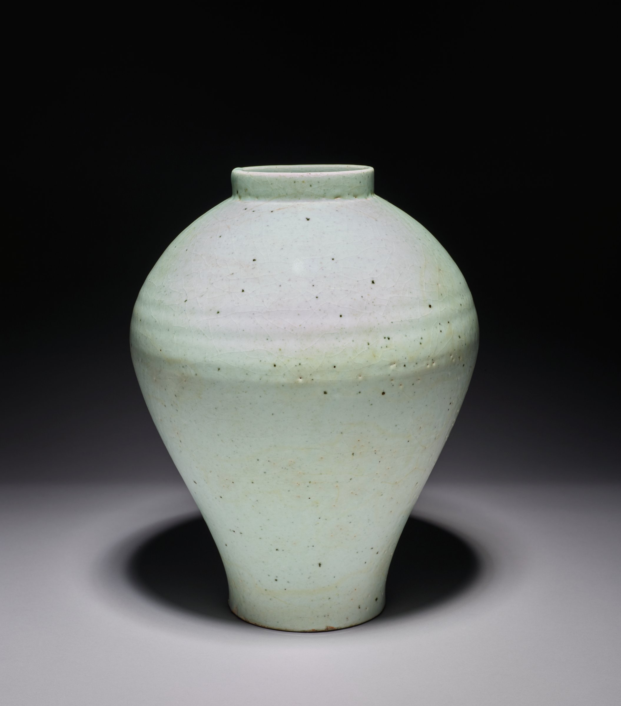 A Korean whiteware most likely used as floral vase (often silk or paper flowers) for aristocrats. The body is covered with a crackled transparent glaze of pronounced blue cast that makes the vase show a lightly celadon blue hue. The vase has a sloping shoulder and an upright circular rim and is resting on a raised ring foot with patch of kiln grit on recessed base. Lightweight, possibly 19th or even 20th century